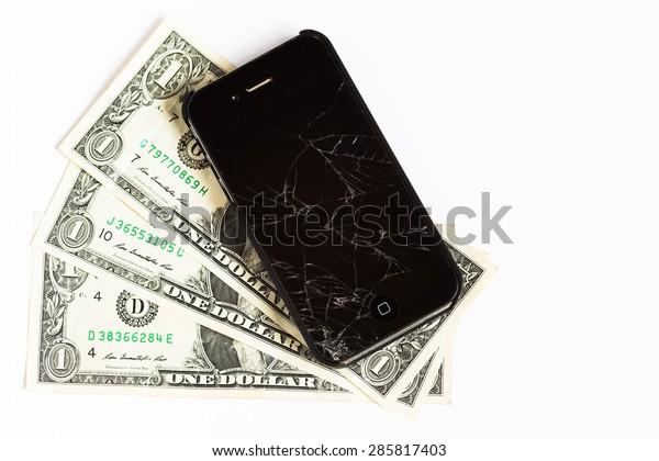 ATLANTA, GA - JUNE 1, 2015: Apple iPhone cellphone laying on dollars bills. Apple Inc. is an American multinational technology company.