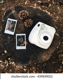 ATLANTA, GA - JUNE 18TH, 2016: Fujifilm Instax white camera laid out on a nature atmosphere background with some prints.