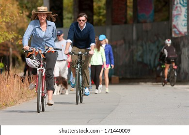 ATLANTA, GA - NOVEMBER 2, 2013:  A couple rides bikes under an overpass that is part of the 22- mile Atlanta Beltline, an urban redevelopment project, on November 2, 2013 in Atlanta, GA.