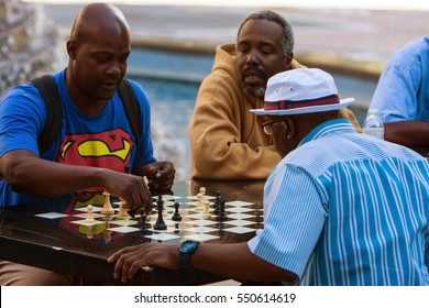 ATLANTA, GA - OCTOBER 8:  African-American men play chess on a community chess table at Woodruff Park in downtown Atlanta on October 8, 2016 in Atlanta, GA.