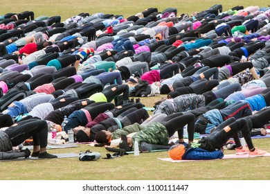 Atlanta, GA / USA - April 8, 2018:  Dozens of people do bridge pose as they take part in a massive group yoga class in Piedmont Park on April 8, 2018 in Atlanta, GA.