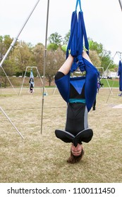 Atlanta, GA / USA - April 8, 2018:  A woman hangs upside down using fabric attached to poles, as she takes part in an aerial yoga class in Piedmont Park on April 8, 2018 in Atlanta, GA.