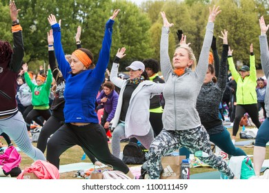 Atlanta, GA / USA - April 8, 2018:  Women do a version of the warrior pose as they take part in a massive group yoga class in Piedmont Park on April 8, 2018 in Atlanta, GA.