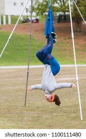 Atlanta, GA / USA - April 8, 2018:  A young woman hangs upside down using fabric attached to poles, as she takes part in an aerial yoga class in Piedmont Park on April 8, 2018 in Atlanta, GA.