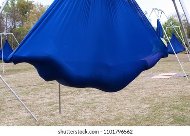 Atlanta, GA / USA - April 8, 2018: A young woman lies suspended in a cocoon of fabric attached to poles, as she takes part in an aerial yoga class in Piedmont Park on April 8, 2018 in Atlanta, GA.