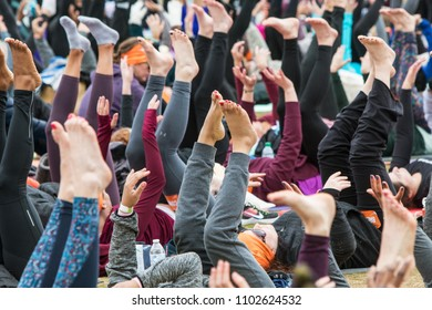 Atlanta, GA / USA - April 8, 2018:  Dozens of people extend legs and feet into the air as they take part in a massive group yoga class in Piedmont Park on April 8, 2018 in Atlanta, GA.