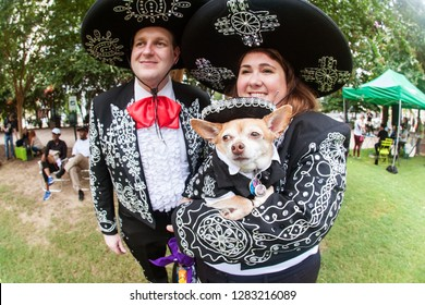 Atlanta, GA / USA - August 18 2018:  A couple and their chihuahua are dressed in mariachi costumes at Doggy Con, a dog costume contest in Woodruff Park on August 18, 2018 in Atlanta, GA.