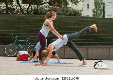 Atlanta, GA / USA - August 18 2018:  A young female yoga instructor teaches yoga positions to women in a free class at Woodruff Park on August 18, 2018 in Atlanta, GA.