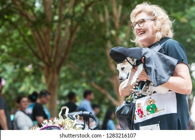 Atlanta, GA / USA - August 18 2018:  A woman carries a small dog dressed like Darth Vader from Star Wars as she and her dog participate in Doggy Con, a dog costume contest in Atlanta, GA.