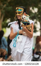 Atlanta, GA / USA - August 18, 2018:  A young woman dressed as an ancient Egyptian carries her small dog dressed as a pharaoh at Doggy Con, a dog costume contest at Woodruff Park in Atlanta.