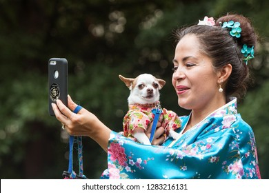 Atlanta, GA / USA - August 18, 2018:  A woman wearing a kimono takes a selfie as she holds her small dog, dressed in a kimono costume, at Doggy Con, a dog costume contest in Woodruff Park in Atlanta.