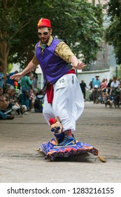 Atlanta, GA / USA - August 18, 2018:  A costumed dog rides with its owner on a motorized skateboard made to look like Aladdin's flying carpet at Doggy Con, a dog costume event in Atlanta, GA.