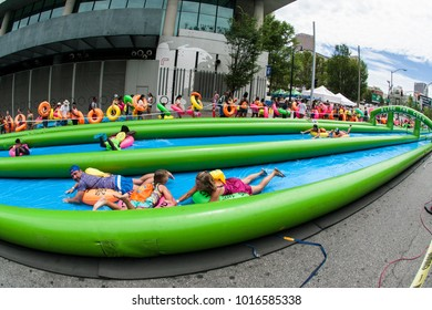 Atlanta, GA, USA - July 15, 2017:  Hundreds of people with innertubes enjoy participating in a giant downhill waterslide at the Slide The City event on July 15, 2017 in Atlanta, GA.