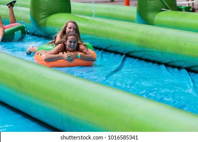 Atlanta, GA, USA - July 15, 2017:  Teenage girls laugh as they travel down a giant slip-and-slide in an innertube, at the Slide The City event on July 15, 2017 in Atlanta, GA.
