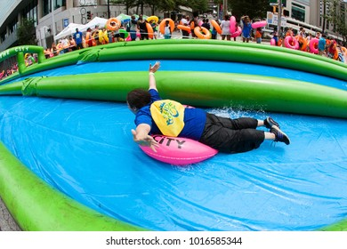 Atlanta, GA, USA - July 15, 2017:  A woman joyfully rides an innertube down a giant water slide on a city street, at the Slide The City event on July 15, 2017 in Atlanta, GA.