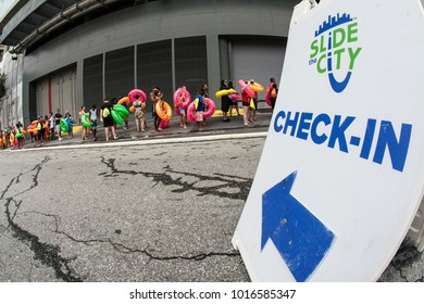 Atlanta, GA, USA - July 15, 2017:  People carrying innertubes stand in line  around a city block, waiting their turn on the water slide at the Slide The City event, on July 15, 2017 in Atlanta, GA.