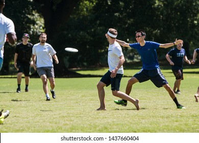 Atlanta, GA / USA - July 28, 2018:  A man tosses a frisbee to a teammate in an ultimate frisbee game in Piedmont Park on July 28, 2018 in Atlanta, GA.