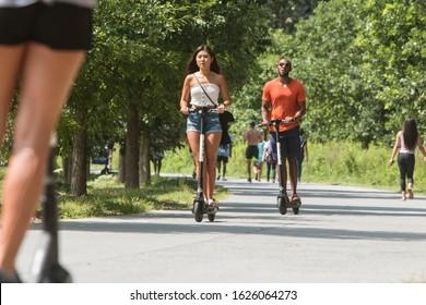 Atlanta, GA / USA - July 6, 2019:  People ride motorized scooters along the Atlanta Belt Line at the Old Fourth Ward Park, on July 6, 2019 in Atlanta, GA.