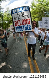 """Atlanta, GA / USA - June 30 2018:  A man walks holding a sign that says """"Families belong together"""" at an immigration law protest and march on June 30, 2018 in Atlanta, GA."""