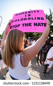 """Atlanta, GA / USA - June 30 2018:  A woman holds a sign saying """"Humanity is colorblind - Stop the hate"""" at an immigration law protest and march on June 30, 2018 in Atlanta, GA."""