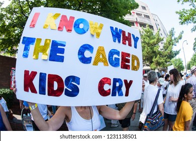 """Atlanta, GA / USA - June 30 2018:  A woman holds a sign saying """"I know why the caged kids cry"""" at an immigration law protest and march on June 30, 2018 in Atlanta, GA."""