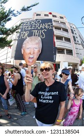 """Atlanta, GA / USA - June 30 2018:  A woman holds a sign saying """"Zero tolerance for this"""" showing Donald Trump's face, at an immigration law protest and march on June 30, 2018 in Atlanta, GA."""