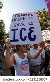 """Atlanta, GA / USA - June 30 2018:  A woman holds a sign saying """"Trump's heart is as cold as ICE"""" at an immigration law protest and march on June 30, 2018 in Atlanta, GA."""