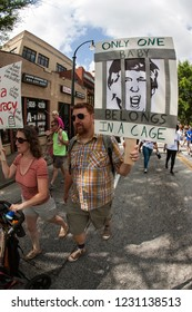 """Atlanta, GA / USA - June 30 2018:  A man walks holding sign of Donald Trump behind bars that says """"Only one baby belongs in a cage"""" at an immigration law protest on June 30, 2018 in Atlanta, GA."""