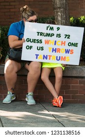 """Atlanta, GA / USA - June 30 2018:  A child holds a sign saying 'I'm 9. Trump is 72.  Guess which one of us throws tantrums"""" at an immigration law protest  and march on June 30, 2018 in Atlanta, GA."""