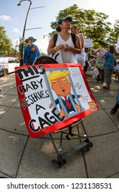 Atlanta, GA / USA - June 30 2018:  A woman transports an anti-Trump sign in a baby stroller, as hundreds of people protest immigration laws and Trump's policies at a rally on June 30, 2018 in Atlanta.