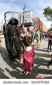 Atlanta, GA, USA - October 21, 2017:  A boy interacts with person wearing  grim reaper costume and holding scythe, before the start of the annual Little Five Points Halloween Parade on October 21, 201