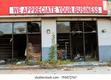 """Atlanta, GA, USA - September 23, 2017:  A sign reading """"We appreciate your business"""" sits above a vandalized, burned out and abandoned small business on September 23, 2017 in Atlanta, GA."""
