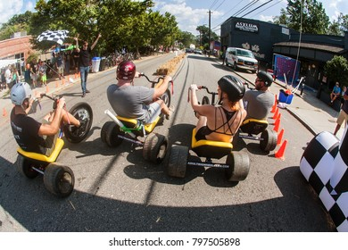 Atlanta, GA, USA - September 23, 2017:  People race each other on adult big wheels in a friendly competition at the East Atlanta Strut, a fall festival on September 23, 2017 in Atlanta, GA.