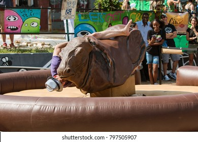 Atlanta, GA, USA - September 23, 2017:  A young man desperately tries to stay on a mechanical bull as he starts falling, at the East Atlanta Strut, a festival on September 23, 2017 in Atlanta, GA.