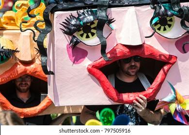 Atlanta, GA, USA - September 23, 2017:  Men wearing huge handmade custom masks walk in the East Atlanta Strut festival parade on September 23, 2017 in Atlanta, GA.