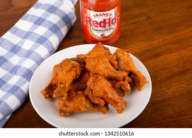 ATLANTA, GEORGIA - April 19, 2017:  Buffalo Chicken Wings on a white plate with a bottle of Frank's Red Hot Sauce in background