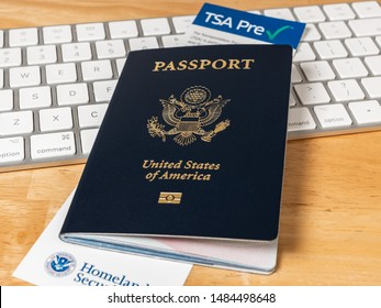 ATLANTA, GEORGIA - AUGUST 21, 2019 : United States of America Passport with Department of Homeland Security TSA Pre Check registration information card. US Passport on desk with computer keyboard.