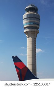 ATLANTA, GEORGIA - AUGUST 27: Delta plane next to Air Traffic Control Tower at Atlanta Hartsfield-Jackson Airport on  August 27, 2012. It has been the world's busiest airport  by  since 1998.