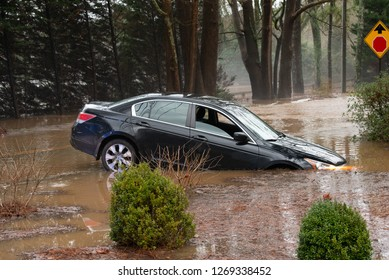 ATLANTA, GEORGIA – DECEMBER 28, 2018: A car is stuck in a ditch after the driver attempted to turn around after encountering floodwaters.