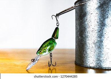 ATLANTA, GEORGIA - DECEMBER 29, 2018 : Fishing lure hanging from metal minnow bucket handle. Bass fishing tackle including crank bait lure with white and wood background.