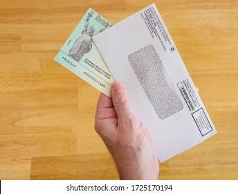 ATLANTA, GEORGIA - May 7, 2020 : United States Treasury Economic Impact check including President Donald J. Trump printed name. Hand holding stimulus check for Coronavirus COVID-19 pandemic relief.