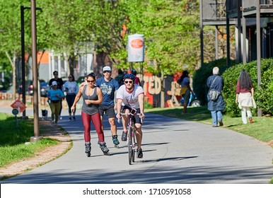 ATLANTA, GEORGIA / UNITED STATES - APRIL 2, 2020: Atlanta Beltline during COVID-19 pandemic, people social distancing while walking and riding bikes.