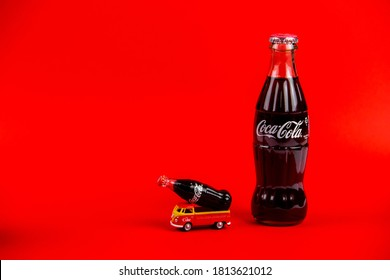 Atlanta, Georgia, USA – April 1, 2020: Vintage die cast toy Transporter T1 with Coca-Cola ad 1960's carrying retro Coca Cola toy bottle and Coca Cola contour bottle isolated on red background .