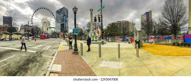 ATLANTA, GEORGIA / USA - August 23, 2019: centennial Olympic Park with Super Bowl decorations on skyscrapers including CNN headquarters, Ferris Wheel, street car, tourists, and locals.