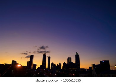 Atlanta, Georgia / USA - January 28, 2012: A dramatic silhouette of a cluster of iconic skyscrapers that define Georgia's Atlanta set against the golden and blue hour after sunset.