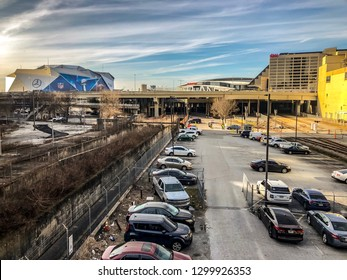ATLANTA, GEORGIA / USA - January 30, 2019: Cars parked at the Gulch and Rail Yard overlooking CNN World Headquarters, State Farm Arena, and Mercedes-Benz Stadium hosting NFL Super Bowl 53.