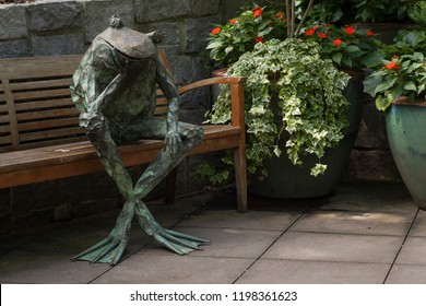 Atlanta, Georgia, USA – July 29, 2015: Copper sculpture of a frog sitting on a bench in the Atlanta Botanical Garden in Piedmont Park, Midtown