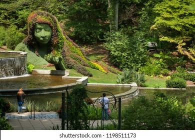Atlanta, Georgia, USA – July 29, 2015: Two visitors contemplate the woman sculpture of the Cascades Garden in the Atlanta Botanical Garden, Piedmont Park, Midtown