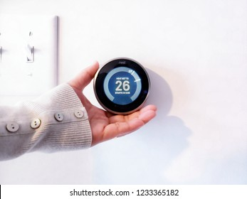 Atlanta, Georgia / USA - Nov 15, 2018 : A women hand adjusting the temperature on modern circle thermostat, Programmable Nest Thermostat - Wireless Learning in white background
