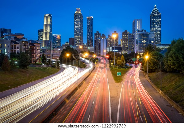 Atlanta skyline during sunset with blue skies from Jackson Street Bridge with light trails of cars during rush hour
